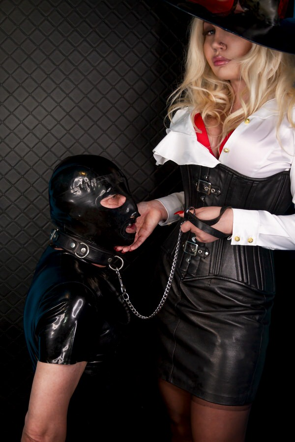 London Dominatrix wearing leather corset with rubber hooded submissive at her feet